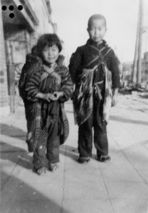 Children of Kamoi. The child on the left is carrying her sibling on her back.